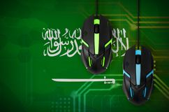 Saudi Arabia flag and two mice with backlight. Online cooperative games. Cyber sport team. Saudi Arabia flag and two modern computer mice with backlight. The stock images
