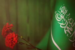 Saudi Arabia flag for honour of veterans day or memorial day with two red carnation flowers. Glory to the Saudi Arabia heroes of w. Saudi Arabia flag with two royalty free stock photography