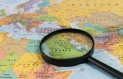 Map of Saudi Arabia through magnifying glass on a world map. Saudi Arabia map through magnifying glass on a world map Royalty Free Stock Image