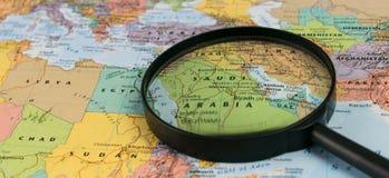 Map of Saudi Arabia through magnifying glass on a world map. Saudi Arabia map through magnifying glass on a world map Royalty Free Stock Photo