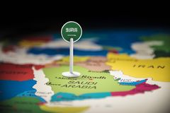 Saudi Arabia marked with a flag on the map.  royalty free stock photos