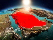 Saudi Arabia in sunrise from orbit. Sunrise above Saudi Arabia highlighted in red on model of planet Earth in space with visible country borders. 3D illustration Stock Photos