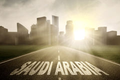 Saudi Arabia word on empty road. Highway towards to a town and sunrise with Saudi Arabia word Stock Photography