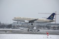 Saudi Arabian Airlines Airbus A320-200 HZ-ASB landing on snowy runway Stock Photography