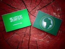 Saudi Arabian flag with African Union flag on a tree stump isola Royalty Free Stock Photos