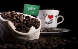 Saudi Arabian flag in a bag with coffee beans  on black Stock Photo