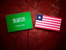 Saudi Arabian flag with Liberian flag on a tree stump isolated Royalty Free Stock Photo