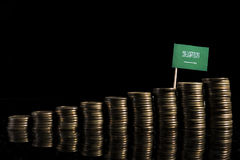 Saudi Arabian flag with lot of coins isolated on black backgroun Royalty Free Stock Photography