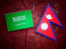 Saudi Arabian flag with Nepali flag on a tree stump isolated Royalty Free Stock Photography