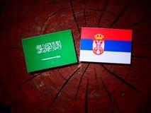 Saudi Arabian flag with Serbian flag on a tree stump isolated Royalty Free Stock Photography