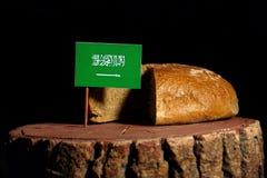 Saudi Arabian flag on a stump with bread Stock Photos