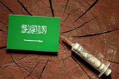 Saudi Arabian flag on a stump with syringe injecting money Royalty Free Stock Images