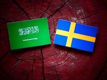 Saudi Arabian flag with Swedish flag on a tree stump  Royalty Free Stock Photos