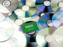 Saudi Arabian flag on top of CD and DVD pile isolated on white. Saudi Arabian flag on top of CD and DVD pile isolated Royalty Free Stock Images