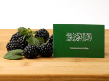 Saudi Arabian flag on a wooden panel with blackberries isolated Royalty Free Stock Photography