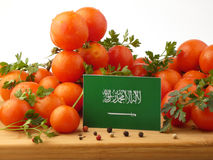 Saudi Arabian flag on a wooden panel with tomatoes isolated on a Royalty Free Stock Photo