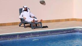 Saudi arabian man talking on phone at swimming pool stock footage