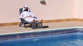 Saudi arabian man using his phone at swimming pool stock video footage