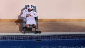 Saudi arabian man using his phone at swimming pool stock footage
