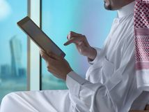 Saudi Arabian Man Using Tablet Beside Window stock photos
