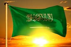 Saudi-Arabien Flagge, die auf dem schönen orange Sonnenuntergang mit Wolkenhintergrund spinnt stockbild
