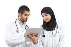 Saudi-arabische Doktoren, die eine Krankengeschichte schauend bestimmen Stockfotografie
