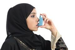 Saudi-arabische Frau, die von einem Asthmainhalator atmet Stockfoto