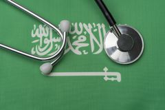 Saudi flag and stethoscope. The concept of medicine. Stethoscope on the flag as a background royalty free stock image