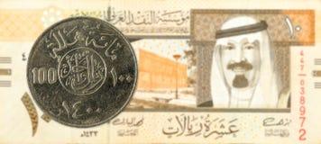100-Saudi Riyal-Münze gegen die 10-Saudi Riyal-Banknote lizenzfreie stockfotos