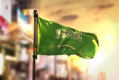 Saudiarabien flagga mot suddig bakgrund för stad på soluppgångBac royaltyfri foto