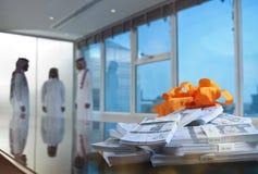 Saudier - arabiska affärsmän i en mötesrum med buntar av pengar på arkivbilder