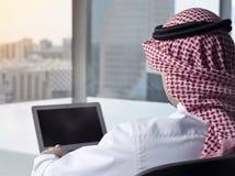 Saudier - hållande ögonen på bärbar dator för arabisk man på att beskåda för arbete arkivbild