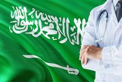 Saudische Doktorstellung mit Stethoskop auf Saudi-Arabien Flaggenhintergrund Nationales Gesundheitssystemkonzept, medizinisches T lizenzfreie stockfotografie