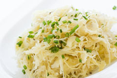 Sauerkraut. Tasty Sauerkraut with leek decorated as closeup on a white dish Stock Photos