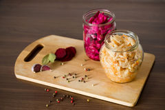 Sauerkraut with beets and spices in a glass jar on wooden backgr royalty free stock images