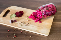 Sauerkraut with beets and spices in a glass jar on wooden backgr stock photos