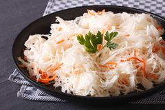 Sauerkraut and carrots in a black plate close-up horizontal Stock Photography
