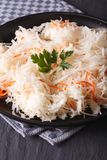 Sauerkraut and carrots in a black plate close-up vertical Stock Images
