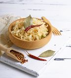 Sauerkraut with carrots and onions. Sauerkraut with carrots and green onions in a brown wooden bowl on a white board Stock Photo
