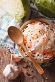 Sauerkraut and carrots in a wooden plate close up vertical top v Royalty Free Stock Photos