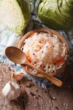 Sauerkraut and carrots in a wooden plate vertical top view. Sauerkraut and carrots in a wooden plate vertical view from above, rustic style Stock Image