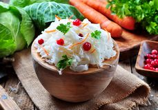 Sauerkraut with cranberries and carrots in a wooden bowl on a wooden background. rustic style. Selective focus. Stock Photo
