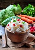 Sauerkraut with cranberries and carrots in a wooden bowl on a wooden background. rustic style. Selective focus. Stock Photos