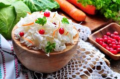 Sauerkraut with cranberries and carrots in a wooden bowl on a wooden background. rustic style. Selective focus. Stock Photography