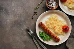 Sauerkraut with grilled sausage on a dark rustic background. Overhead view, copy space stock image