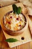 Sauerkraut - Kwaśna kapusta - na drewnianym pucharze z podpalanymi liśćmi Zdjęcie Stock