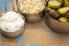 Sauerkraut, pickles and yogurt. Sauerkraut, cucumber pickles and yogurt - popular probiotic fermented food - three measuring cups against rustic wood royalty free stock images