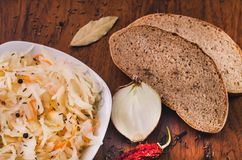 A sauerkraut plate, a laurel leaf, cumin seeds, a cut onion, a red hot dried chili pepper and a slice of bread on a wooden table royalty free stock images