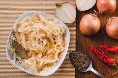 A sauerkraut plate with a laurel leaf and cumin seeds and onions, red dried hot peppers and a spoon of cumin seeds royalty free stock photography