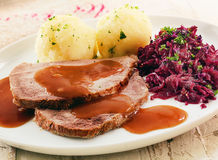 Sauerkraut, potatoes , meat and gravy. Sauerkraut made from red cabbage, potatoes , sliced meat and gravy served on plate, close up view Stock Photography